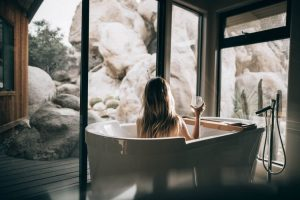 A bathtub near a huge window offering stunning views